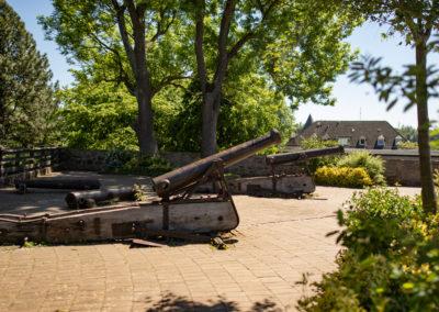 Ein Siegener Denkmal mit zwei alten Kanonen an einem sonnigen Tag. Diese stehen zwischen grünen Bäumen.