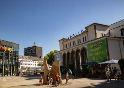 Apollo Theater. An einem sonnigen Tag entstanden. Links davon befindet sich der Laden MyToys und davor befinden sich Menschen, die sich am Springbrunnen die Füße abkühlen.